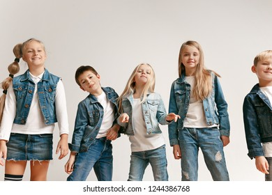 The portrait of cute little kids boy and girls in stylish jeans clothes looking at camera against white studio wall. Kids fashion and happy emotions concept