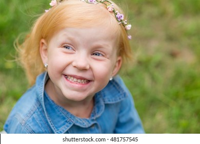 Portrait of a cute little pin-up girl on the nature. Portrait of a beautiful redhead child with a sweet smile. The charming redhead kid
