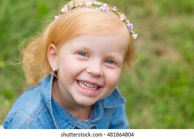 Portrait of a cute little pinup girl on the nature. Portrait of a beautiful redhead child with a sweet smile. The charming redhead kid