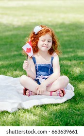 Portrait of cute little red-haired Caucasian girl child holding Canadian flag with red maple leaf sitting on grass in park outside celebrating Canada Day anniversary
