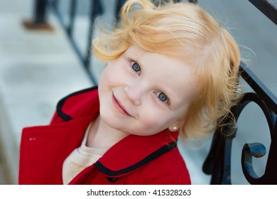 portrait of a cute little redhead  girl in red coat outdoors in summer