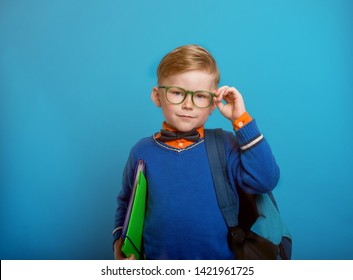 Portrait of a cute little school boy. Back to school. Success, bright idea, creative ideas and innovation concept. Portrait of happy kid in glasses. Blond hear boy isolated on blue background.