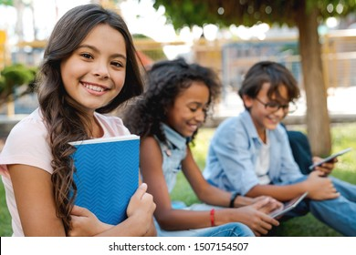 Portrait of cute little school girl and childrens on background with backpacks and notebooks outdoor