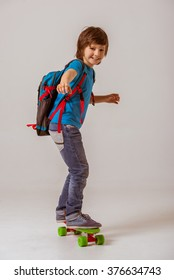 Portrait of a cute little schoolboy in a blue t-shirt with a backpack looking in camera and smiling while skateboarding on a gray background