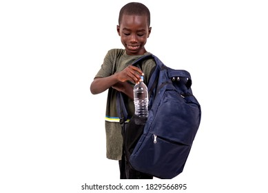 portrait of a cute little schoolboy boy taking a plastic mineral water bottle inside his backpack pocket while smiling.