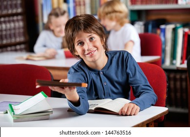 Portrait of cute little schoolboy giving book while sitting at table in library with classmates in background