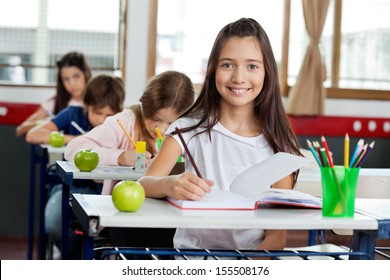 Portrait of cute little schoolgirl writing in book with classmates in background at classroom