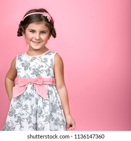 Portrait of cute little smiling girl on pink background. Space for text.