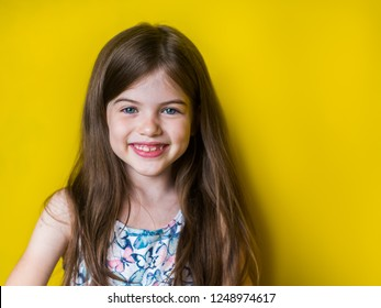 portrait of cute little smiling girl on yellow background