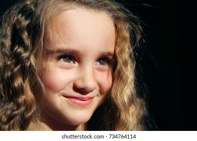 Portrait of cute little smiling girl looking to the right on black background. Horizontal frame