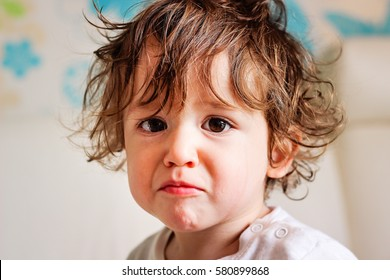 Portrait of a cute little toddler boy kid curly hair smiling and crying fun face expression