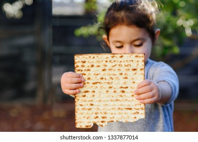 Portrait of the cute little toddler holding matzah. Jewish girl eating matzo (unleavened bread)  in Jewish holidays Passover. Pesach invitation or greeting card.