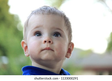 Portrait of a cute, lovable baby boy looking up with a serious face and observing expresion