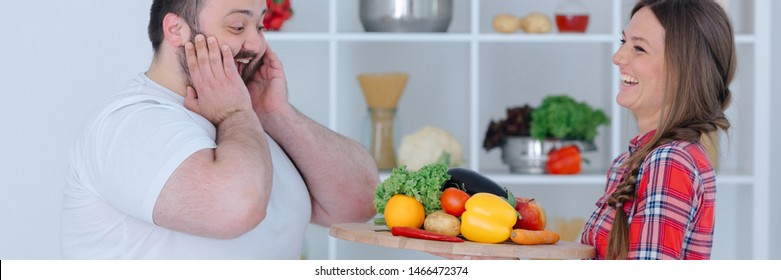 Portrait of cute lovers fooling around in modern trendy kitchen. Gorgeous woman presenting vegetables as sweet cake. Overweight man look surprised. Great cuisine and healthy food concept
