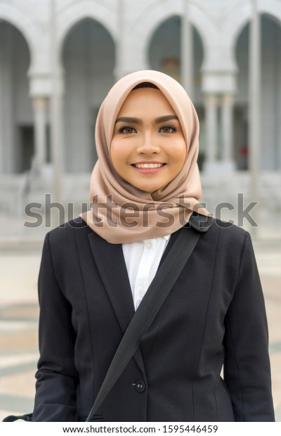 Portrait of Cute Malay Woman wearing hijab outdoor and smile