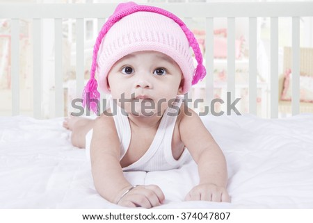 Portrait of cute male baby lying on bed while wearing hat with pink color d1a3d743eaa7