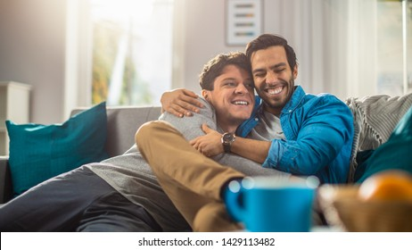Portrait of a Cute Male Queer Couple at Home. They Sit on a Sofa and Look at the Camera. Partner Embraces His Lover from Behind. They are Happy and Smiling. Room Has Modern Interior.