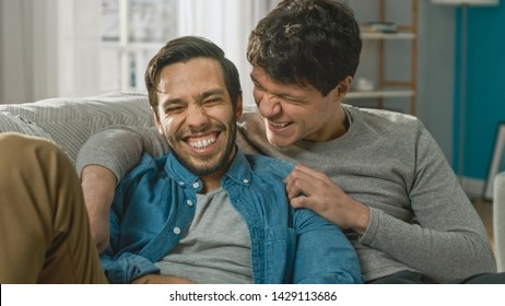 Portrait of a Cute Male Queer Couple at Home. They Sit on a Sofa and Joking. Partner Embraces His Lover from Behind. They are Happy and Smiling. Room Has Modern Interior.