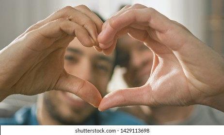 Portrait of a Cute Male Queer Couple at Home Sitting on a Sofaand Making a Heart Symbol with Their Hands. Room Has Modern Interior.