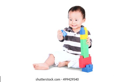 Portrait of a cute male toddler sitting in the studio while playing with toys, isolated on white background