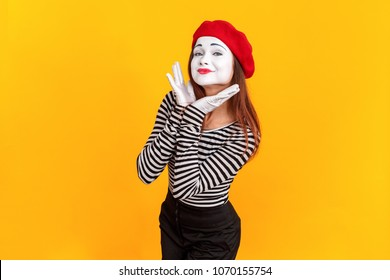 Portrait of cute mime woman showing perfect white skin. Emotions and feelings concept. Indoor shot, yellow background