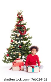 Portrait of cute mixed race little boy sitting on floor near Christmas tree with gift box in his hands