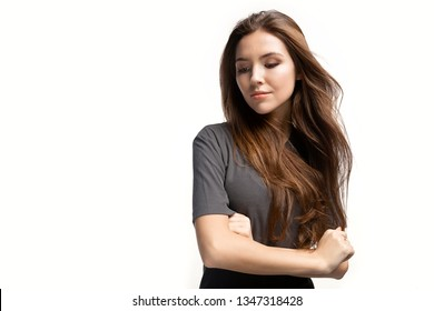 Portrait of cute model with crossed arms. Woman with brunette straight hair wearing in grey shirt. Thoughtful girl lowering eyes. Isolated on white background. Copy space in left side