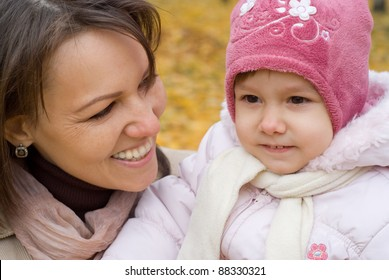 portrait of a cute mom with daughter in forest
