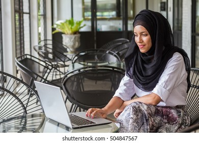 Portrait cute muslim woman sitting and use laptop computer.