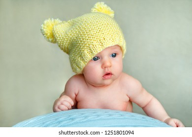 Portrait of a cute newborn baby girl in yellow knitted hat posing on big ball at home