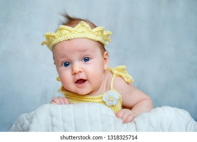 Portrait of a cute newborn baby girl in yellow knitted crown lying on her stomach in bedroom