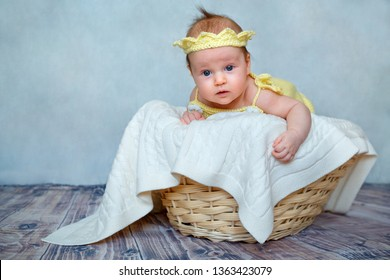 Portrait of a cute newborn baby girl in yellow knitted crown lying on her stomach in wooden basket at home