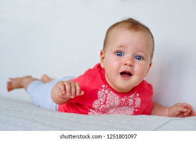 Portrait of a cute newborn baby lying on her stomach and learning to crawl in bedroom