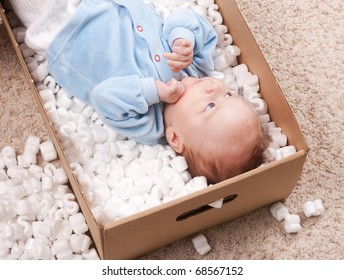 Portrait if cute newborn baby lying in open post box with filler on carpet. Small baby resting in package and smiling for parents.