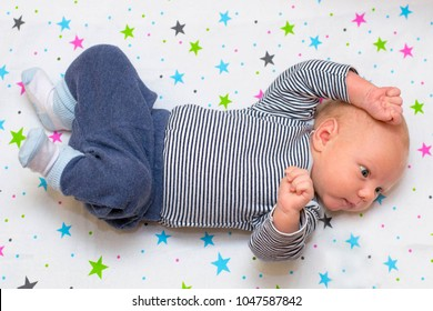 Portrait of a cute newborn baby who lies on his back in a crib, top view