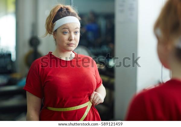 Porträt süßer, fettleibiger Frau, die im Fitnessraum gegen Spiegel steht und die Taillengröße mit Klebeband nach dem Training misst, verärgert und verwirrt aussieht