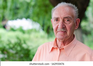 portrait of a cute old man at park