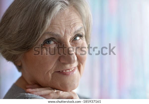 Portrait of a cute old woman on colored background