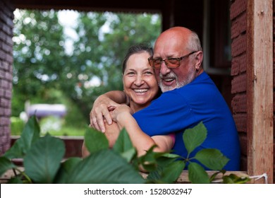 Portrait of cute older men and women on   porch of   country house.