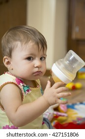 Portrait of cute one year old baby girl looking at camera and holding a feeding bottle
