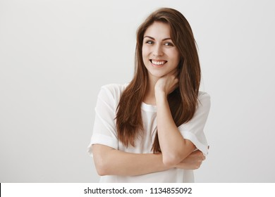 Portrait of cute ordinary caucasian girl feeling insecure or uncomfortable, smiling and touching neck with hand, giving speech in front of crowd, standing against gray background in white shirt