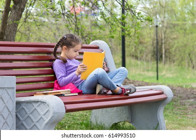 Portrait of cute pensive little girl sitting on the wooden bench with open book in her hands outdoors