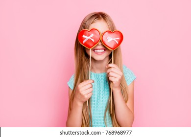 Portrait of cute playful dreamy with toothy smile beautiful girl fooling around, she is hiding her eyes behind cookies in shape of red heart with small bows, isolated on vivid pink background