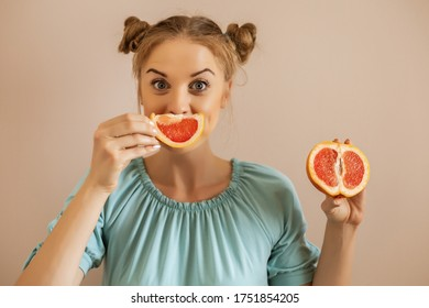 Portrait of cute playful woman holding slices of grapefruit.Toned image.