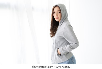 Portrait of a cute positive Asian woman in gray hoodie standing near window relaxing in living room at her home