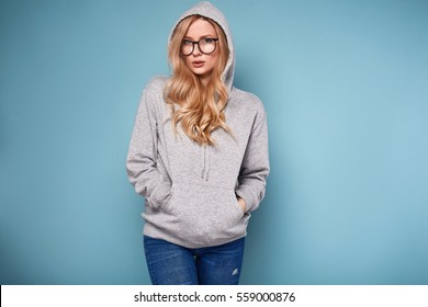 Portrait of a cute positive blonde woman in gray hoodie and glasses on bright background in studio