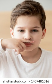 Portrait of cute preschooler boy hold fingers with moustache drawing above lip look at camera, little child posing for picture, congratulate greeting with father day, next male generation offspring