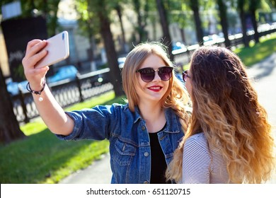 portrait of cute pretty best friends girls, hug and having fun together, kisses, smiling, joy, sisters Wear summer sunglasses and make photos,of their weekends.Selfie portrait