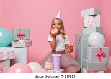 Portrait of a cute pretty little girl in a birthday hat celebrating while sitting in a pile of present boxes and eating donuts isolated over pink background