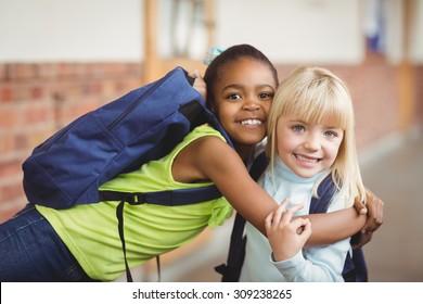 Portrait of cute pupils embracing at corridor in school